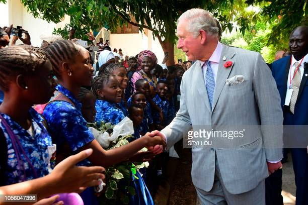 Britain's Prince Charles , the Prince of Wales, speaks with children as he arrives to visit a Malaria research center in Banjul as part of an...