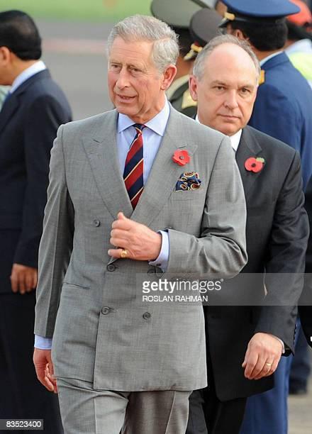 Britain's Prince Charles walks along the red carpet followed by British Ambassador to Indonesia Martin Hatfull upon his arrival at Halim...
