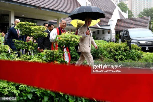 Britain's Prince Charles walks under an umbrella after visiting the StMary's Cathedral in Kuala Lumpur on November 4 2017 Prince Charles and his wife...