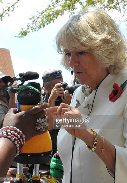 Britain's Prince Charles wife Camilla looks at a Ndebele doll dressed in Ndebele tribe cloths during a tour at Freedom Square of Soweto township on...