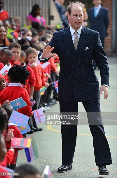 Britain's Prince Edward Earl of Wessex is welcomed by children during a visit to Robert Browning School in London on March 10 2014 Prince Edward...