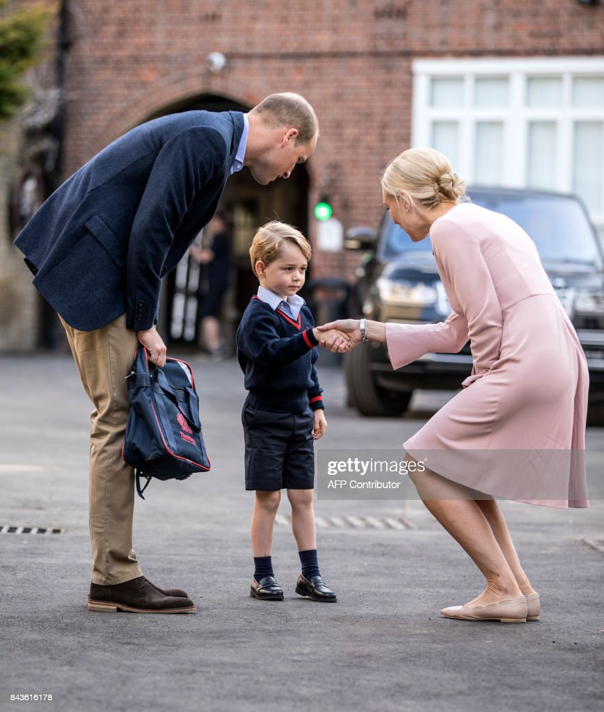 Britain's Prince George (C) accompanied by Britain's Prince William (L), Duke of Cambridge arrives for his first day of school at Thomas's school in Battersea where he is met by Helen Haslem (R) head of the lower school. /