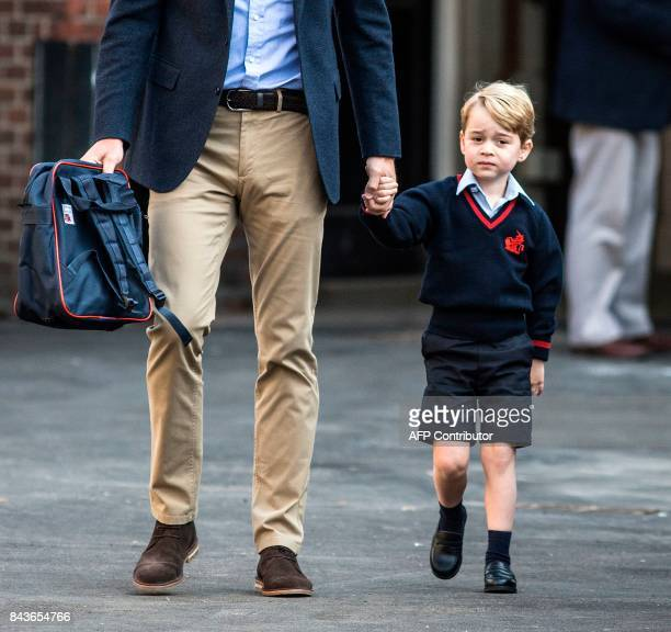 Britain's Prince George accompanied by Britain's Prince William, Duke of Cambridge arrives for his first day of school at Thomas's school on...