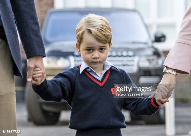 Britain's Prince George accompanied by Britain's Prince William , Duke of Cambridge arrives for his first day of school at Thomas's school where he...