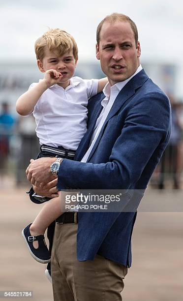 Britain's Prince George is carried by his father Prince William as they visit the Royal International Air Tattoo at RAF Fairford in western England,...