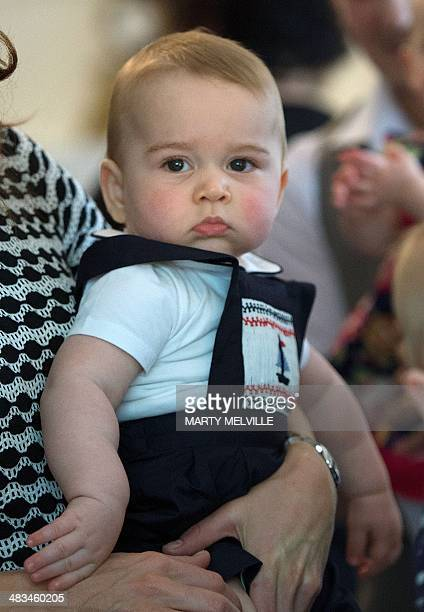 Britain's Prince George is held by his mother Catherine, the Duchess of Cambridge, during a visit to the Plunket nurse and parents group at...