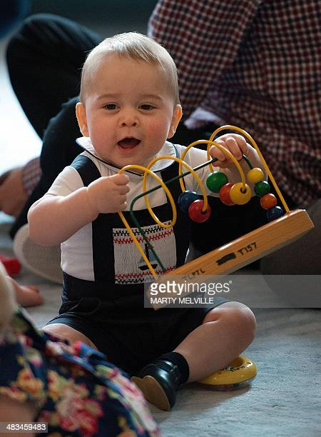 Britain's Prince George plays with toys during a visit to the Plunket nurse and parents group at Government House in Wellington on April 9 2014...