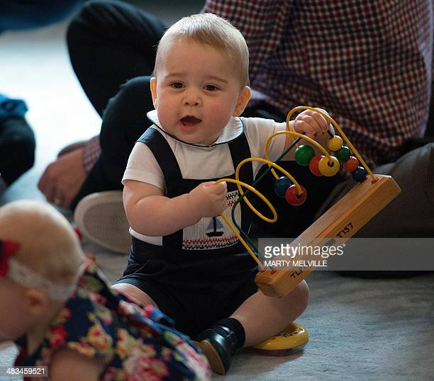 Britain's Prince George plays with toys during a visit to the Plunket nurse and parents group at Government House in Wellington on April 9, 2014....