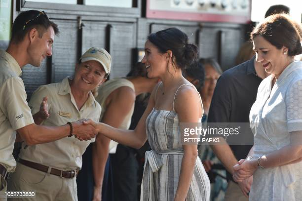 Britain's Prince Harry and and his wife Meghan the Duchess of Sussex greet well wishers as they arrive on the pier on Fraser Island in Queensland on...