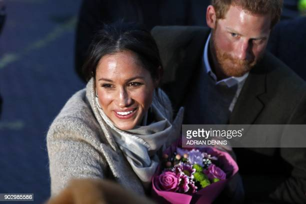Britain's Prince Harry and fiancée US actress Meghan Markle meet wellwishers as they leave after a visit to Reprezent 1073FM community radio station...