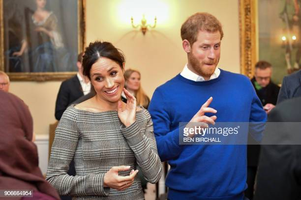 Britain's Prince Harry and his fiancée US actress Meghan Markle chat with people inside the Drawing Room during a visit at Cardiff Castle in Cardiff...