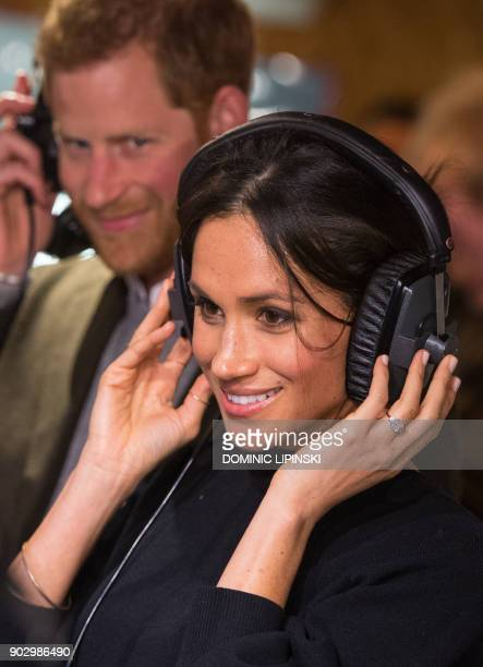 Britain's Prince Harry and his fiancée US actress Meghan Markle listen to a broadcast through headphones during a visit to Reprezent 1073FM community...