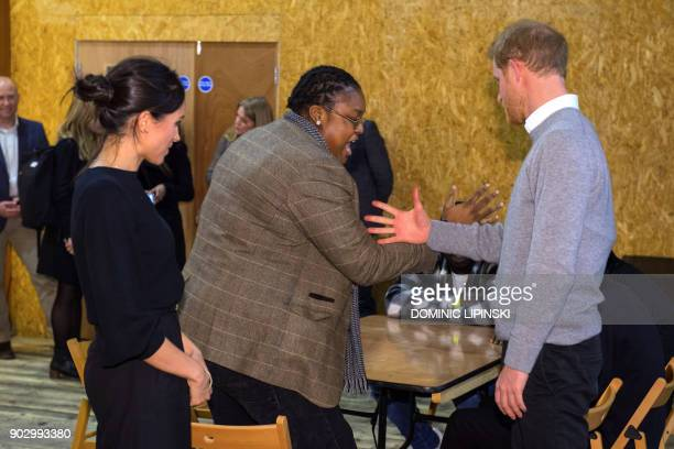 Britain's Prince Harry and his fiancée US actress Meghan Markle meet radio DJ Remi Aderemi during a visit to Reprezent 1073FM community radio station...