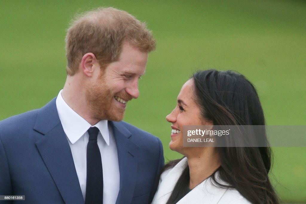TOPSHOT - Britain's Prince Harry and his fiancée US actress Meghan Markle pose for a photograph in the Sunken Garden at Kensington Palace in west London on November 27, 2017, following the announcement of their engagement. Britain's Prince Harry will marry his US actress girlfriend Meghan Markle early next year after the couple became engaged earlier this month, Clarence House announced on Monday. / AFP PHOTO / Daniel LEAL
