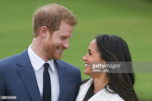 TOPSHOT Britain's Prince Harry and his fiancée US actress Meghan Markle pose for a photograph in the Sunken Garden at Kensington Palace in west...