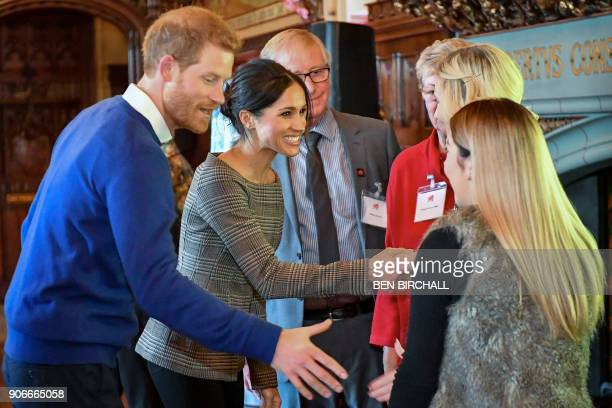 Britain's Prince Harry and his fiancée US actress Meghan Markle shake hands with guests during a visit at Cardiff Castle in Cardiff south Wales on...