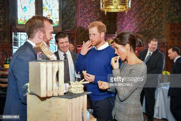 Britain's Prince Harry and his fiancée US actress Meghan Markle taste traditional Welsh cakes during a visit at Cardiff Castle in Cardiff south Wales...