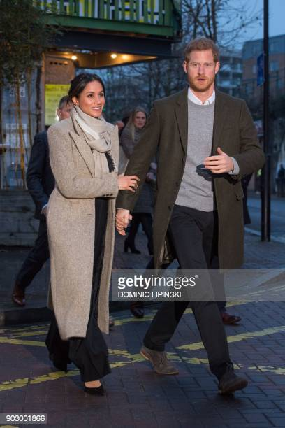 Britain's Prince Harry and his fiancée US actress Meghan Markle walk out to meet wellwishers as they leave after a visit to Reprezent 1073FM...