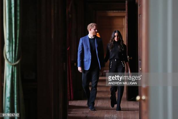 Britain's Prince Harry and his fiancée US actress Meghan Markle walk through the corridors of the Palace of Holyroodhouse on their way to a reception...