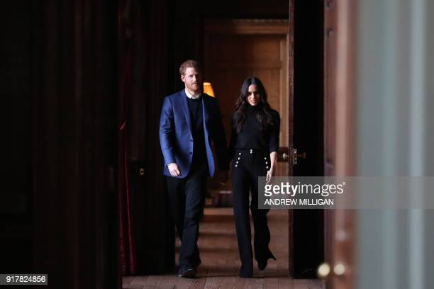 TOPSHOT Britain's Prince Harry and his fiancée US actress Meghan Markle walk through the corridors of the Palace of Holyroodhouse on their way to a...