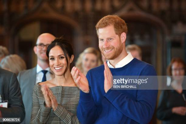 Britain's Prince Harry and his fiancée US actress Meghan Markle watch a performace during a visit to Cardiff Castle in Cardiff south Wales on January...