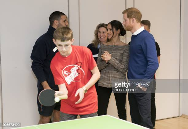 Britain's Prince Harry and his fiancée US actress Meghan Markle watch a game of table tennis during their visit to Star Hub community and leisure...