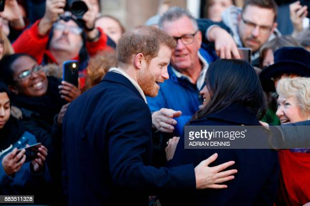 Britain's Prince Harry and his fiancee US actress Meghan Markle gesture as they arrive to attend a Terrence Higgins Trust World AIDS Day charity fair...