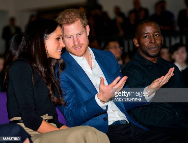 Britain's Prince Harry and his fiancee US actress Meghan Markle gesture at a 'kick boxing' presentation during their visit to Nottingham Academy in...