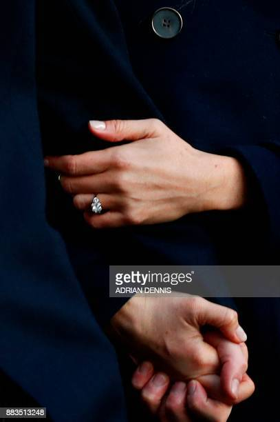 Britain's Prince Harry and his fiancee US actress Meghan Markle clasp hands and display her engagemaent ring as they arrive to attend a Terrence...