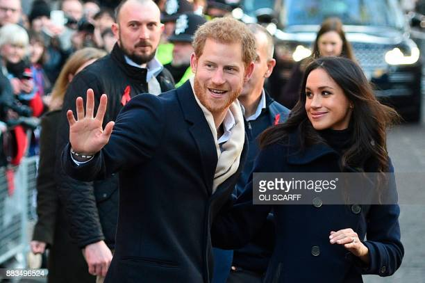 TOPSHOT Britain's Prince Harry and his fiancee US actress Meghan Markle greet wellwishers on a walkabout as they arrive for an engagement at...