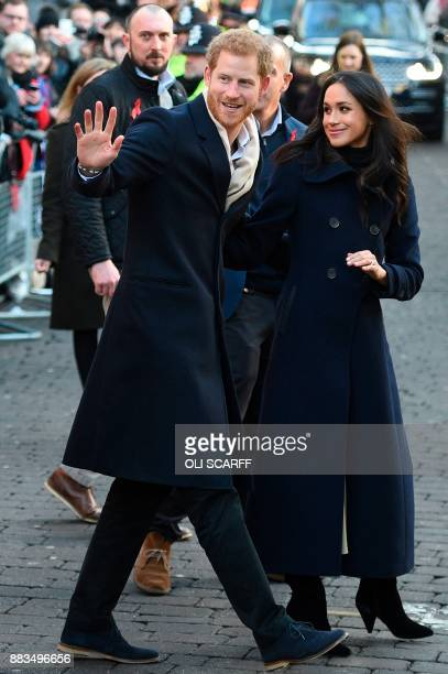 Britain's Prince Harry and his fiancee US actress Meghan Markle greet wellwishers on a walkabout as they arrive for an engagement at Nottingham...