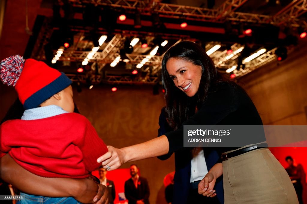 Britain's Prince Harry and his fiancee US actress Meghan Markle greet well-wishers as they tour the Terrence Higgins Trust World AIDS Day charity fair at Nottingham Contemporary in Nottingham, central England, on December 1, 2017. Prince Harry and Meghan Markle visited Nottingham in their first set of engagements together since announcing their engagement. During their first engagament of the day at a Terrence Higgins Trust World AIDS Day charity fair the prince and Markle met representatives from a number of institutes and charities that do specific work around HIV/AIDS. / AFP PHOTO / POOL AND AFP PHOTO / Adrian DENNIS