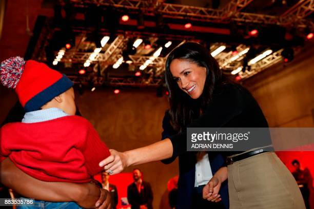 Britain's Prince Harry and his fiancee US actress Meghan Markle greet well-wishers as they tour the Terrence Higgins Trust World AIDS Day charity...
