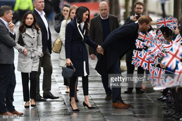 Britain's Prince Harry and his fiancee US actress Meghan Markle greet wellwishers as they arrive at Millennium Point to attend an event hosted by by...