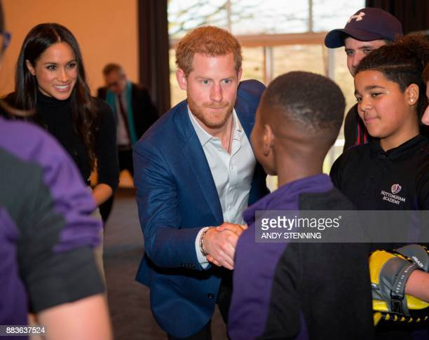 Britain's Prince Harry and his fiancee US actress Meghan Markle meet participants of a 'kick boxing' presentation during their visit to Nottingham...