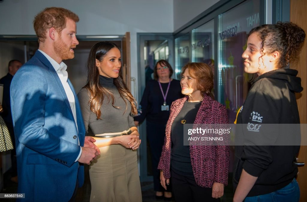Britain's Prince Harry and his fiancee, US actress Meghan Markle meet Chantelle Stefanovic, (R), a project coordinator at the Full Effect programme which seeks to combat youth violence, during their visit to Nottingham Academy in Nottingham, central England, on December 1, 2017. Prince Harry and his American actress fiancee Meghan Markle were welcomed by hundreds of people on their first royal visit as a couple since announcing their engagement this week. / AFP PHOTO / POOL / Andy Stenning