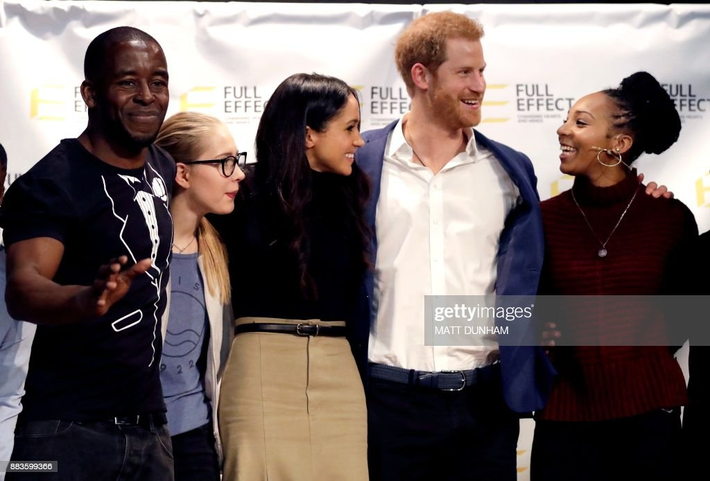 Britain's Prince Harry (2R) and his fiancee US actress Meghan Markle (3R) pose for a photograph with the cast and crew of a hip hop opera performed by young people involved in the Full Effect programme at the Nottingham Academy school in Nottingham on December 1, 2017. Prince Harry and Meghan Markle visited Nottingham in their first set of engagements together since announcing their engagement. At Nottingham Academy the prince and Markle discussed the Full Effect programme which supports children and young people in the St Ann's area of Nottingham from becoming involved in youth violence and crime through a combination of early intervention, mentorship, and training. / AFP PHOTO / POOL / Matt Dunham