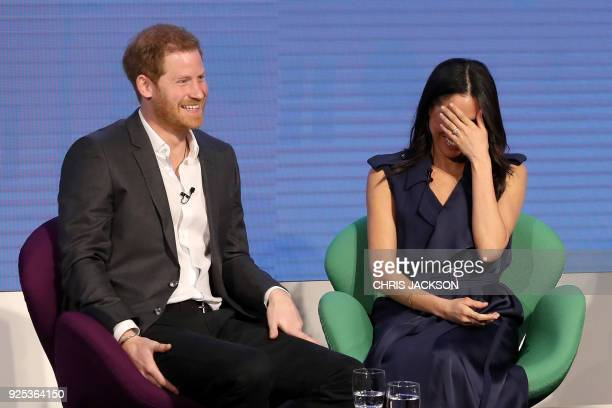 Britain's Prince Harry and his fiancee US actress Meghan Markle share a joke as they attend the first annual Royal Foundation Forum on February 28...