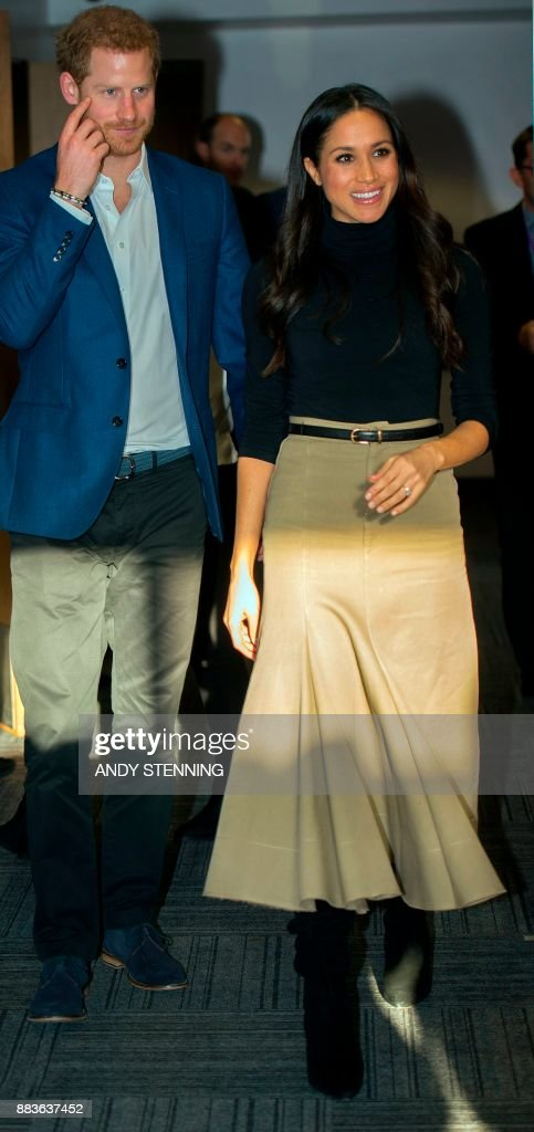 Britain's Prince Harry and his fiancee US actress Meghan Markle gesture during their visit to Nottingham Academy in Nottingham, central England, on December 1, 2017. Prince Harry and his American actress fiancee Meghan Markle were welcomed by hundreds of people on their first royal visit as a couple since announcing their engagement this week. / AFP PHOTO / POOL / Andy Stenning