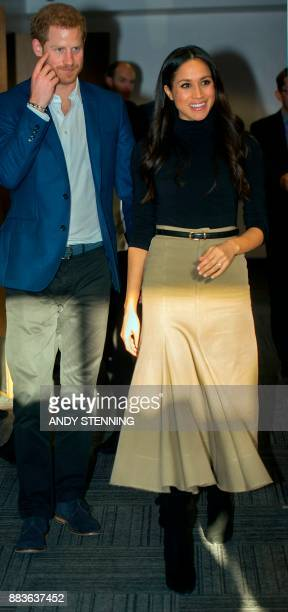 Britain's Prince Harry and his fiancee US actress Meghan Markle gesture during their visit to Nottingham Academy in Nottingham central England on...