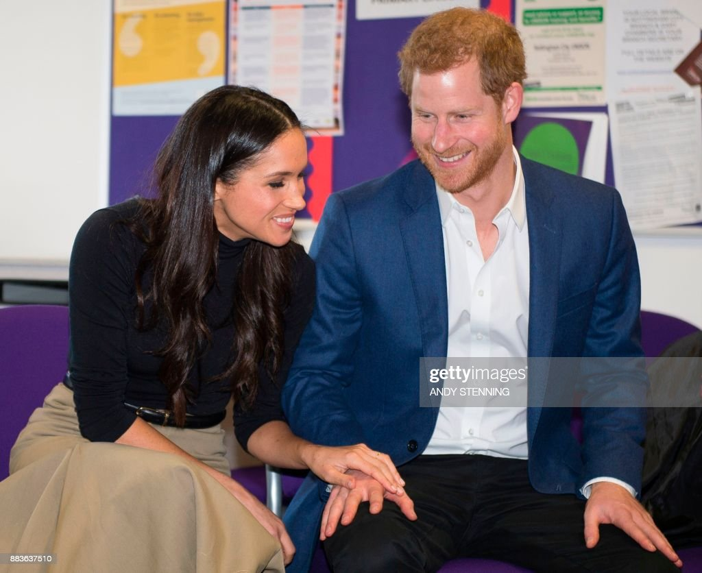 Britain's Prince Harry and his fiancee, US actress Meghan Markle gesture during their visit to Nottingham Academy in Nottingham, central England, on December 1, 2017. Prince Harry and his American actress fiancee Meghan Markle were welcomed by hundreds of people on their first royal visit as a couple since announcing their engagement this week. / AFP PHOTO / POOL / Andy Stenning