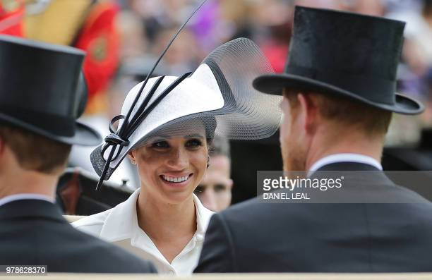 TOPSHOT Britain's Prince Harry and his wife Britain's Meghan Duchess of Sussex arrive on day one of the Royal Ascot horse racing meet in Ascot west...