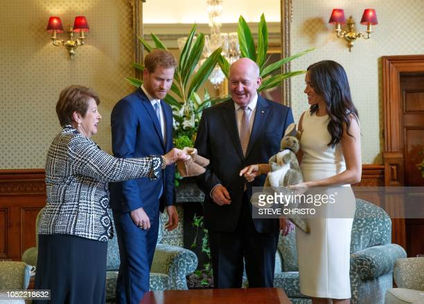 TOPSHOT Britain's Prince Harry and his wife Meghan are presented with presents for for a baby from Australian GovernorGeneral Sir Peter Cosgrove and...