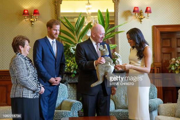 Britain's Prince Harry and his wife Meghan are presented with presents for a baby from Australian GovernorGeneral Peter Cosgrove and his wife at...