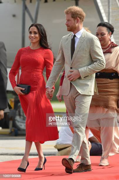 TOPSHOT Britain's Prince Harry and his wife Meghan Duchess of Sussex arrive at Fua'amotu airport in Tonga on October 25 2018 Prince Harry and his...