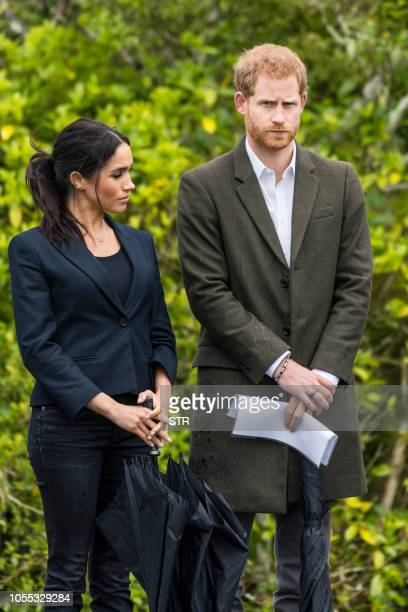 Britain's Prince Harry and his wife Meghan, Duchess of Sussex arrive to unveil a plaque dedicating 20 hectares of native bush to the Queen's...
