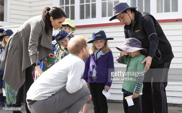 Britain's Prince Harry and his wife Meghan, Duchess of Sussex attempt to coax a smile from 5-year-old Joe Young while meeting with students from...