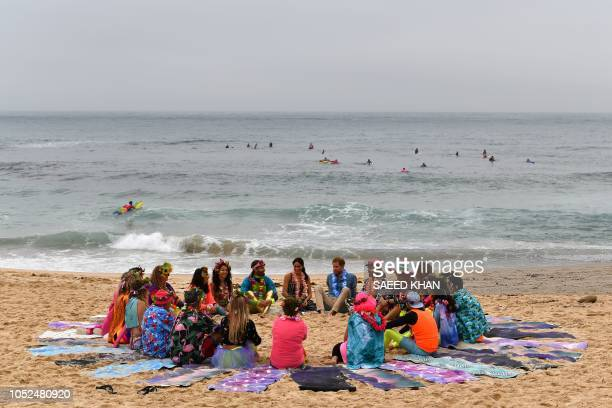 TOPSHOT Britain's Prince Harry and his wife Meghan Duchess of Sussex attend a 'Fluro Friday' session run by OneWave a local surfing community group...