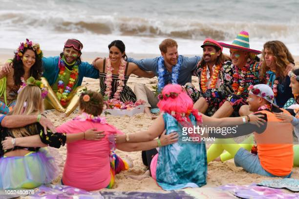TOPSHOT Britain's Prince Harry and his wife Meghan Duchess of Sussex join a circle during a 'Fluro Friday' session run by OneWave a local surfing...