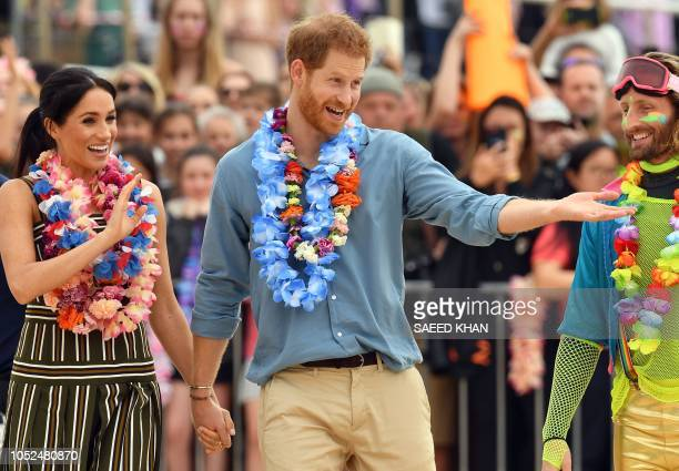 TOPSHOT Britain's Prince Harry and his wife Meghan Duchess of Sussex leave after a 'Fluro Friday' session run by OneWave a local surfing community...